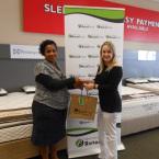 Natelie Kriel from Beacon Bay Retail Park handing over gifts to winner Belinda Mitchell